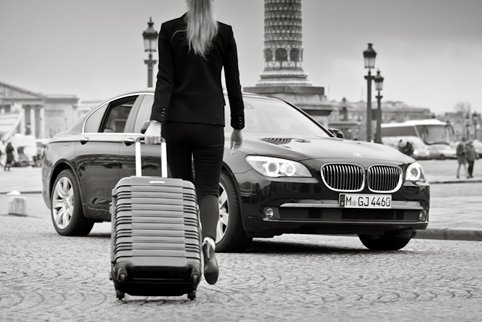 A client with luggage next to a black car